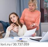 Купить «Woman is outraged of utility bills and quarreling with her mother», фото № 30737059, снято 15 февраля 2018 г. (c) Яков Филимонов / Фотобанк Лори