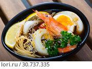 Купить «Image of spicy pan-Asian soup with squid, shrimp, egg noodles and sesame», фото № 30737335, снято 21 ноября 2019 г. (c) Яков Филимонов / Фотобанк Лори
