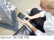 A young woman sitting at a charging station and looking at her smartphone. Recharging mobile phones from free charge station at the airport. Стоковое фото, фотограф Matej Kastelic / Фотобанк Лори