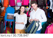 Купить «couple examining various sports bags in sports store», фото № 30738847, снято 22 ноября 2016 г. (c) Яков Филимонов / Фотобанк Лори