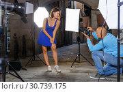 Купить «Professional photo shooting outdoors. Attractive female model posing to photographer on city street», фото № 30739175, снято 5 октября 2018 г. (c) Яков Филимонов / Фотобанк Лори