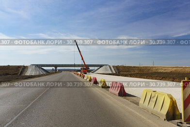 Разделенная наполненными водой барьерами строящаяся скоростная дорога Таврида вблизи развилки в Багерово. Крым