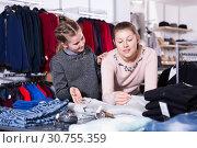 Купить «Girl with mother shopping for clothes», фото № 30755359, снято 21 марта 2018 г. (c) Яков Филимонов / Фотобанк Лори