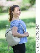 Жизнерадостная женщина гуляет в парке летом с рюкзаком на плече. Стоковое фото, фотограф Кекяляйнен Андрей / Фотобанк Лори