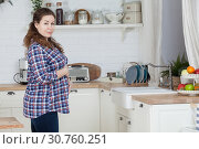 Pregnant woman housewife standing on kitchen and holding her large tummy. Стоковое фото, фотограф Кекяляйнен Андрей / Фотобанк Лори