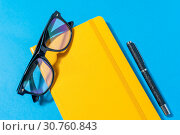 Купить «Yellow notebook, eyeglasses on blue background.», фото № 30760843, снято 20 мая 2019 г. (c) Pavel Biryukov / Фотобанк Лори