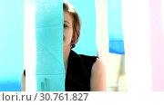 Купить «Cute girl posing among multicolored ribbons», видеоролик № 30761827, снято 2 мая 2019 г. (c) Ekaterina Demidova / Фотобанк Лори