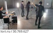 Купить «A young group playing rock music in a spacious hargar», видеоролик № 30769627, снято 6 июля 2020 г. (c) Константин Шишкин / Фотобанк Лори