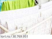 Купить «White and colored linen and towels to be dried on the clothesline», фото № 30769951, снято 2 октября 2018 г. (c) Tetiana Chugunova / Фотобанк Лори