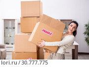 Купить «Young woman moving to new flat», фото № 30777775, снято 30 января 2019 г. (c) Elnur / Фотобанк Лори
