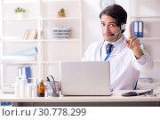 Купить «Young male doctor in telemedicine concept», фото № 30778299, снято 7 декабря 2018 г. (c) Elnur / Фотобанк Лори