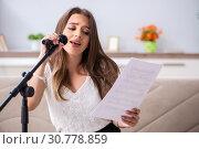 Купить «Female beautiful musician singing at home», фото № 30778859, снято 1 октября 2018 г. (c) Elnur / Фотобанк Лори