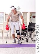 Купить «Injured young man doing exercises at home», фото № 30779595, снято 15 февраля 2019 г. (c) Elnur / Фотобанк Лори