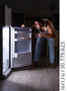 Купить «Man breaking diet at night near fridge», фото № 30779623, снято 8 февраля 2019 г. (c) Elnur / Фотобанк Лори