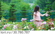 Young girl in a flower garden among beautiful roses. Smell of roses. Стоковое видео, видеограф Дмитрий Травников / Фотобанк Лори
