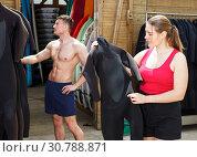 Купить «Girl choosing wetsuit in surf club», фото № 30788871, снято 30 апреля 2018 г. (c) Яков Филимонов / Фотобанк Лори