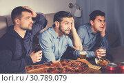 Купить «Worried concentrated men watching sporting match on tv with beer», фото № 30789079, снято 10 января 2018 г. (c) Яков Филимонов / Фотобанк Лори