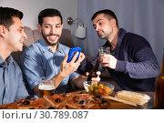 Купить «Male friends sitting with phone at home», фото № 30789087, снято 10 января 2018 г. (c) Яков Филимонов / Фотобанк Лори