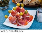 Купить «Traditional Spanish tapas - rolls of ham served with green olives», фото № 30789375, снято 24 мая 2019 г. (c) Яков Филимонов / Фотобанк Лори