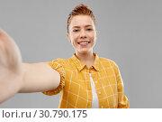 Купить «smiling red haired teenage girl taking selfie», фото № 30790175, снято 28 февраля 2019 г. (c) Syda Productions / Фотобанк Лори