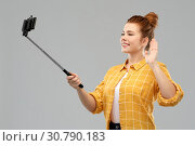Купить «happy teenage girl taking picture by selfie stick», фото № 30790183, снято 28 февраля 2019 г. (c) Syda Productions / Фотобанк Лори