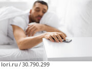 sleepy young man reaching for smartphone in bed. Стоковое фото, фотограф Syda Productions / Фотобанк Лори