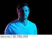 Купить «portrait of man over neon lights in dark room», фото № 30790359, снято 3 февраля 2019 г. (c) Syda Productions / Фотобанк Лори