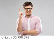 Купить «smiling young man in glasses pointing finger up», фото № 30790375, снято 3 февраля 2019 г. (c) Syda Productions / Фотобанк Лори