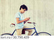 man with smartphone and fixed gear bike on street. Стоковое фото, фотограф Syda Productions / Фотобанк Лори