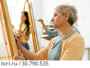 Купить «senior woman drawing on easel at art school studio», фото № 30790535, снято 26 мая 2017 г. (c) Syda Productions / Фотобанк Лори