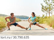 Купить «smiling couple stretching legs on beach», фото № 30790635, снято 1 августа 2018 г. (c) Syda Productions / Фотобанк Лори