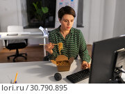 Купить «businesswoman eating and working at night office», фото № 30790895, снято 23 февраля 2019 г. (c) Syda Productions / Фотобанк Лори