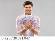 Купить «smiling young man with fan of euro money over grey», фото № 30791047, снято 3 февраля 2019 г. (c) Syda Productions / Фотобанк Лори