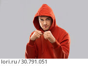 Купить «man in red hoodie fighting with fists or boxing», фото № 30791051, снято 3 февраля 2019 г. (c) Syda Productions / Фотобанк Лори