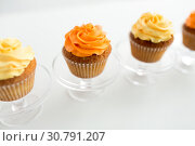 Купить «cupcakes with frosting on confectionery stands», фото № 30791207, снято 6 июля 2018 г. (c) Syda Productions / Фотобанк Лори