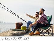 Купить «happy friends with fishing rods on pier», фото № 30791227, снято 8 сентября 2018 г. (c) Syda Productions / Фотобанк Лори