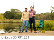 Купить «friends with fishing rod and net at lake or river», фото № 30791231, снято 8 сентября 2018 г. (c) Syda Productions / Фотобанк Лори