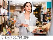Купить «Attractive Brazilian girl discussing books with other visitor of bookstore», фото № 30791299, снято 18 января 2018 г. (c) Яков Филимонов / Фотобанк Лори