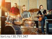 Купить «Passionate emotional female drummer with her bandmates practicin», фото № 30791347, снято 26 октября 2018 г. (c) Яков Филимонов / Фотобанк Лори