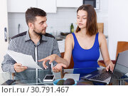 Купить «Serious young man and woman with financial documents near laptop», фото № 30791467, снято 6 июля 2018 г. (c) Яков Филимонов / Фотобанк Лори