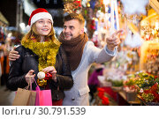 Купить «Couple in hat at Christmas Fair, man points to decorations», фото № 30791539, снято 14 декабря 2017 г. (c) Яков Филимонов / Фотобанк Лори