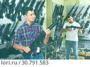 Купить «Friends choosing air-powered gun», фото № 30791583, снято 4 июля 2017 г. (c) Яков Филимонов / Фотобанк Лори