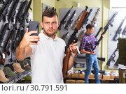 Купить «Man taking selfie with weapon», фото № 30791591, снято 4 июля 2017 г. (c) Яков Филимонов / Фотобанк Лори