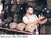 Купить «Young guys choosing helmet in military shop», фото № 30791603, снято 4 июля 2017 г. (c) Яков Филимонов / Фотобанк Лори