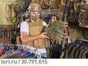 Купить «Young guy choosing flak jacket in military shop», фото № 30791615, снято 4 июля 2017 г. (c) Яков Филимонов / Фотобанк Лори