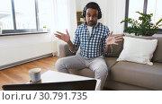Купить «male blogger with headphones videoblogging at home», видеоролик № 30791735, снято 26 апреля 2019 г. (c) Syda Productions / Фотобанк Лори