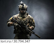 Купить «Army soldier in Combat Uniforms with assault rifle, plate carrier and combat helmet are on, Shemagh Kufiya scarf on his neck. Studio shot, dark background.», фото № 30794347, снято 19 ноября 2016 г. (c) age Fotostock / Фотобанк Лори