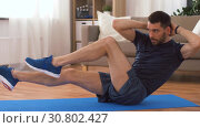 Купить «man making abdominal exercises at home», видеоролик № 30802427, снято 15 мая 2019 г. (c) Syda Productions / Фотобанк Лори