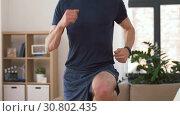 Купить «man with wireless earphones exercising at home», видеоролик № 30802435, снято 15 мая 2019 г. (c) Syda Productions / Фотобанк Лори