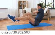 Купить «man making abdominal exercises at home», видеоролик № 30802503, снято 15 мая 2019 г. (c) Syda Productions / Фотобанк Лори
